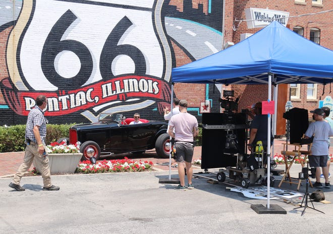 A member of the Good Guys Car Club, which is made up of car enthusiasts from all over the country, gets his picture taken in his ride by a member of the set crew for a commercial that was shot in downtown Pontiac Tuesday. The two entities — the car club and the film crew — arrived in town about the same time.