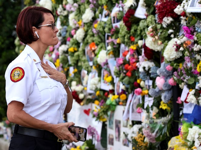 Miami-Dade Fire Rescue Chief Melanie C. Adams visits the makeshift memorial set up near the partially collapsed Champlain Towers South Condo in Surfside, Fla.