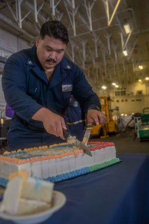 Hospital Corpsman 2nd Class Matthew Ye, from Ridgecrest, California, assigned to USS Gerald R. Ford's (CVN 78) medical department, cuts a ceremonial cake during an award presentation and cake-cutting ceremony following a recent Captain's Cup competition hosted by The Gay, Lesbian and Supporting Sailors association during Pride Month, June 28, 2021.