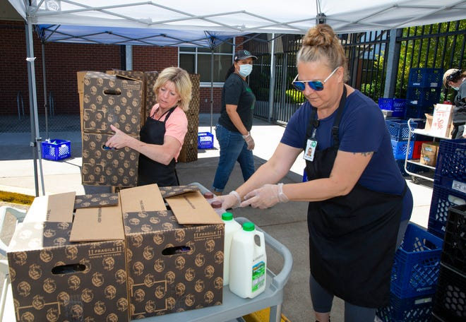 Eugene School District 4J staff including Joannie Weyant, left, Evonne Beckner and Kelly Briggs deliver boxes of food to waiting families lined up in their cars at Cal Young Middle School on Wednesday.