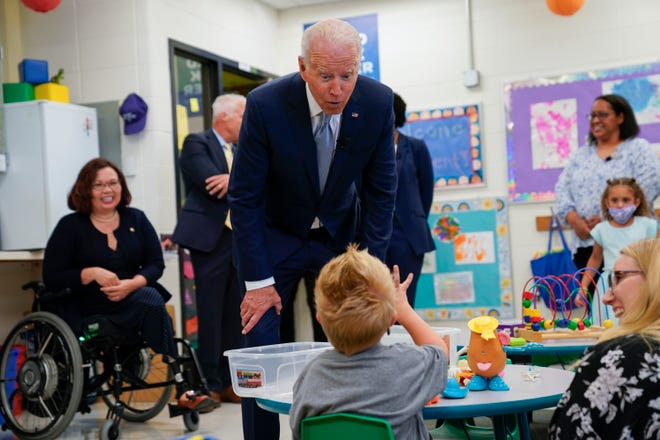 President Joe Biden speaks to a child as he tours a children's learning center at McHenry County College on Wednesday in Crystal Lake. Sen. Tammy Duckworth, R-Ill., left, and President of McHenry County College Clint Gabbard look on.