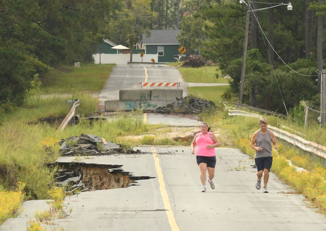 Residents run along Alton Lennon Drive Wednesday Sept. 9, 2020, in Boiling Spring Lakes, N.C., as the dam is still washed away after water from Hurricane Florence overran it in 2018.
