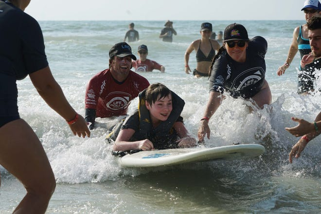 During a 2019 event, supporters of Life Rolls On and Ocean Cure help a youth with disabilities enjoy the ocean at Carolina Beach. [WENDY JACKSON/LIFE ROLLS ON]