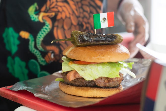 The hamburguesas Mexicana is an American classic with a Mexican twist. Its a traditional hamburger with a grilled and sliced hotdog layered with avocado, lettuce, tomatoes, onion, jalopeño, ketchup, mustard and topped with a grilled jalopeño and Mexican flag for $9 at the food truck Hamburguesas Mexicanas #1.