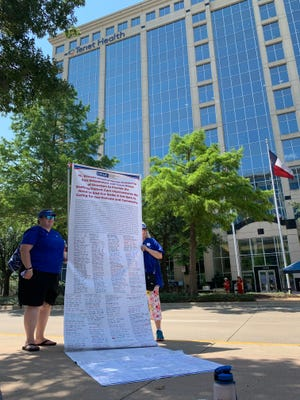 The union nurses brought a 16-foot-long petition signed by over 700 nurses, held up outside Tenet Healthcare headquarters in Dallas, to show Tenet CEO Ron Rittenmeyer.