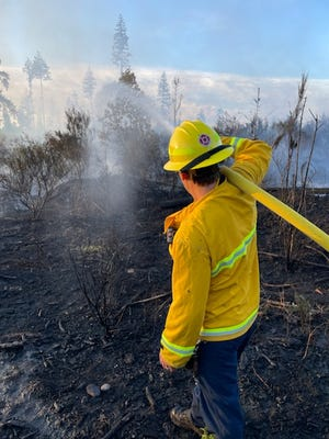 A South Kitsap Fire and Rescue responder works to douse a brush fire in off Wicks Lane Road Tuesday night.