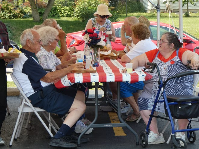 Seniors enjoy a cookout lunch and ice cream outside theCrawford County Council on Aging on Tuesday afternoon as the senior center reopened its doors to the public for the first time since March 2020.