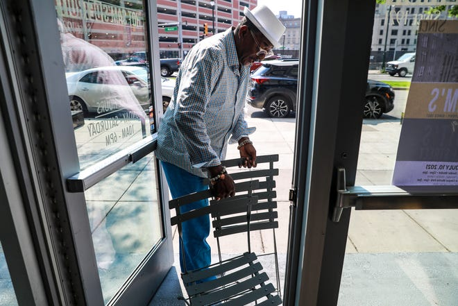 Hot Sam's co-owner Tony Stovall, 69, of Southfield places chairs and a table outside the store on July 7, 2021. Stovall says he wants people to come to the store for more than shopping. Hot Sam's Detroit is celebrating its 100th year of being in business in downtown Detroit and they'll be hosting a large event at Campus Martius and Cadillac Square this Saturday.