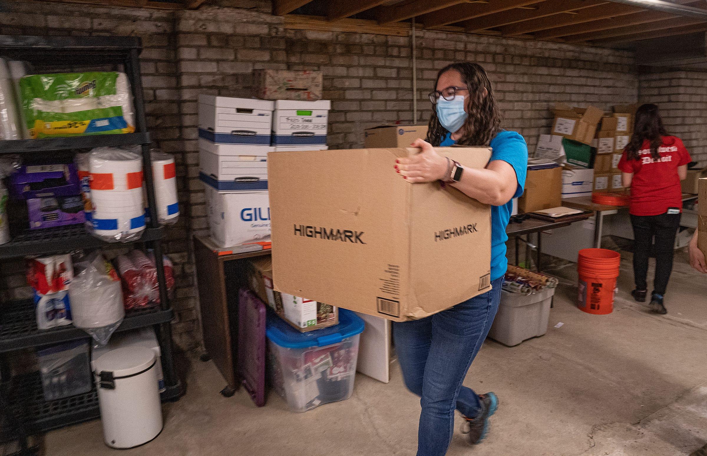 Lindsey Watson, 31 años, organizadora comunitaria de Congress of Communities en Southwest Detroit, mueve una caja el 22 de abril de 2021 para ayudar en las preparaciones de la mudanza a las nuevas oficinas centrales de la organización.