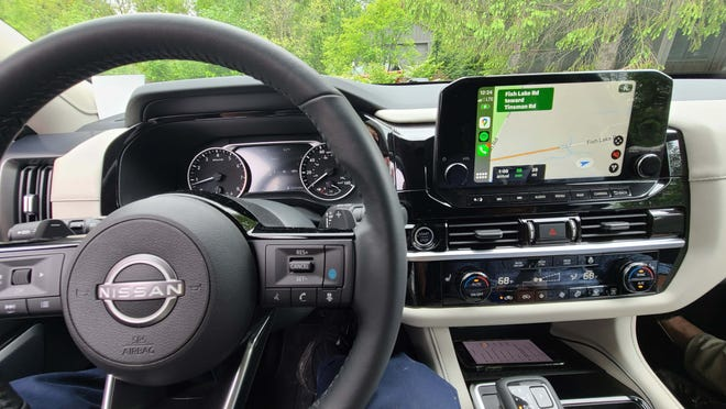Driver's eye view of the 2022 Nissan Pathfinder - digital displays, wireless Apple CarPlay, lots of knobs for easy screen/climate control.
