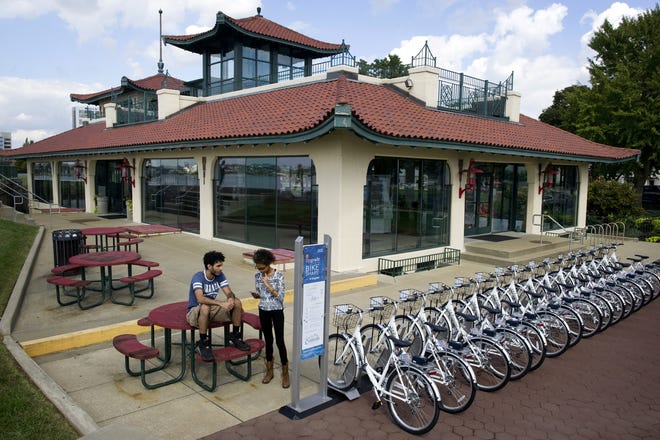 Aydin Harrison, left, and Rebekah Ragland of Evansville register to use the Upgrade Bike Share outside the Pagoda on Monday afternoon, Oct. 3, 2016.
