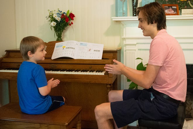 Eli Baumgardner claps along and counts beats with Artie Johnston, 5, at Baumgardner's home in Greenville, S.C. Wednesday, June 30, 2021.