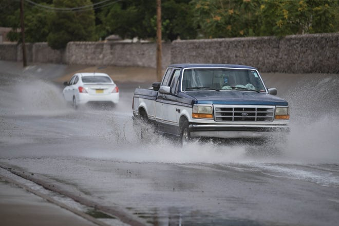 Vehicles drive through a flooded Spruce Avenue in Las Cruces on Wednesday, July 7, 2021.