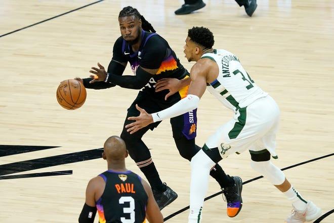 Phoenix Suns forward Jae Crowder passes around Milwaukee Bucks forward Giannis Antetokounmpo, right, to guard Chris Paul (3) during the first half of Game 1 of basketball's NBA Finals, Tuesday, July 6, 2021, in Phoenix. (AP Photo/Matt York)