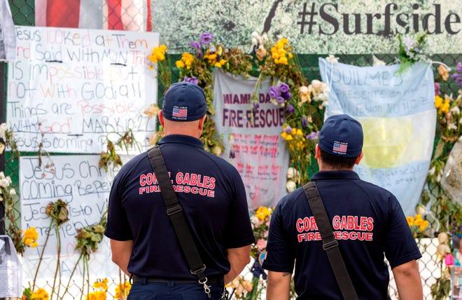Miembros del equipo de Bomberos de Coral Gables visitan el monumento improvisado cerca del edificio de condominios Champlain Towers South derrumbado, el día después de que los edificios siguen siendo demolidos en Surfside, Florida, EE. UU.
