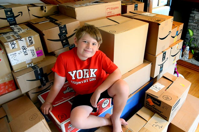 Jameson Shanabrough, 10, sits atop the 4,050 toy donations he received in his latest toy drive at his Spring Garden Township home, Wednesday, July 7, 2021. He'd initially set a goal to get 1,600. Bill Kalina photo