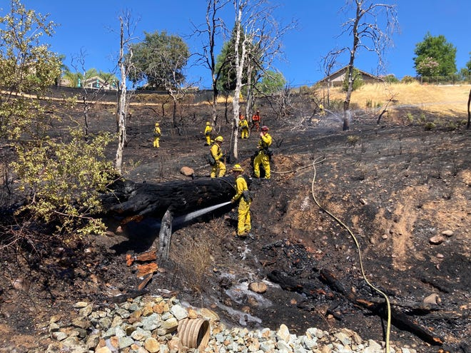 Firefighters mop up after a fire broke out Wednesday, July 7, 2021 off Quarz Hill Road in Redding.