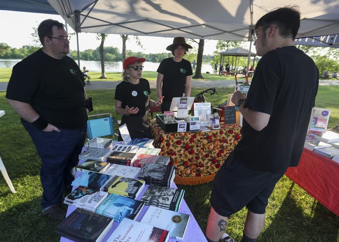 """Matt Zimmerman, Hailey Rae Johnson and Ryan Polacek talk with Peter Munk on July 2 at the Bookshop Co-op tent during Riverfront Rendezvous at Pfiffner Pioneer Park in Stevens Point. The co-op is a justice-driven cooperative bookstore, and the group is raising funds to purchase a vehicle to serve as a """"bookmobile"""" to provide an alternative for communities without bookstores."""