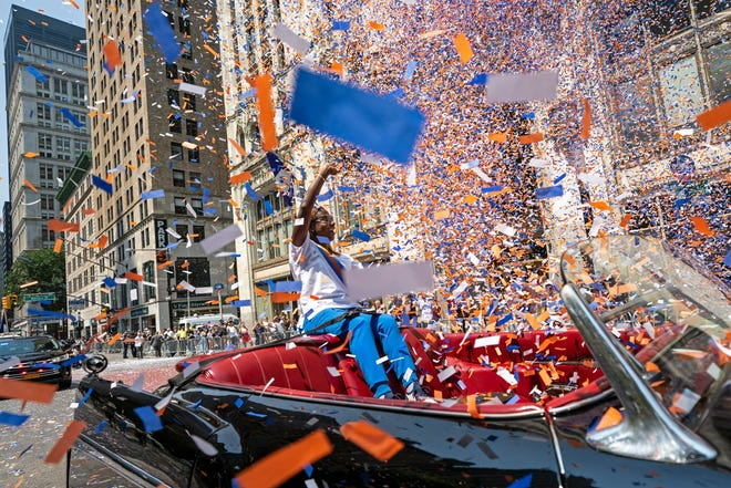 Grand marshal Sandra Lindsay, a health care worker who was the first person in the country to get a COVID-19 vaccine shot, waves to spectators as she leads marchers through the Financial District as confetti falls during a parade honoring essential workers for their efforts in getting New York City through the COVID-19 pandemic, Wednesday, July 7, 2021, in New York.