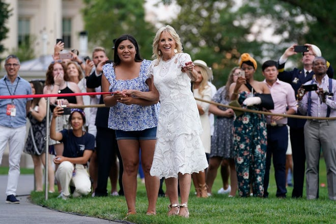 First lady Jill Biden holds a finish line as the Washington Nationals' Racing Presidents mascots race during an Independence Day celebration on the South Lawn of the White House, July 4, 2021.