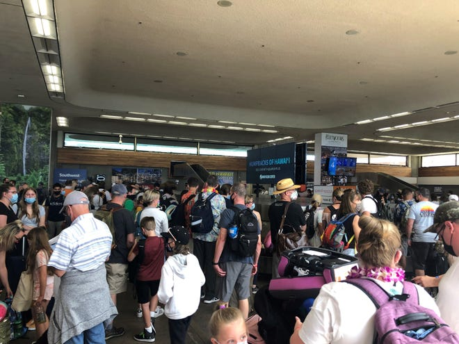 Passengers arriving in Maui wait for bags in the cramped baggage claim area of Kahului Airport. Maui has seen a surge in visitors, and the mayor has proposed a pause in flights.