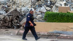 A first responder walks past debris from the imploded portion of the Champlain Towers condo in Surfside, Fla., Tuesday evening, July 6, 2021.