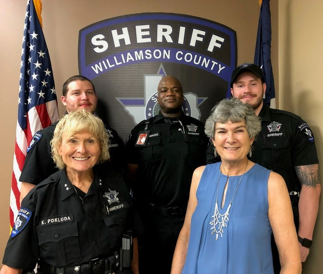 Williamson County Commissioner Terry Cook, bottom right, visits with Assistant Sheriff's Chief Deputy Kathleen Pokluda, bottom left, along with, from left in back, deputy Fernando Ortiz and corrections officers Terry Hargrove and Brandon McBay at the Williamson County sheriff's office in Georgetown.