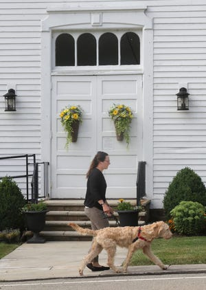 A girl walks her dog in front of the United Methodist Church on the Peninsula.  One of the most picturesque small towns in Ohio, the peninsula's population of less than 600 can reach several thousand people every day with good weather.