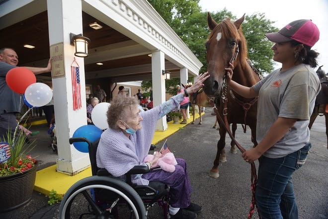 Beaver Valley Healthcare and Rehabilitation resident Nancy Young, 89, pets Maggie the horse while Morgan Cashdollar of Rochester watches. The horse was part of a small parade of horses, a fire truck and other local organizations at the facility Wednesday in South Beaver Township. The parade celebrated the return to visitation and contact for the patients.