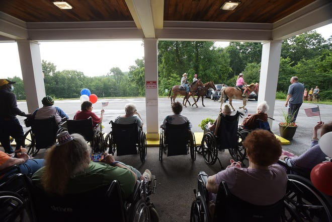 Residents of Beaver Valley Healthcare and Rehabilitation watch a small parade of horses, a fire truck and other local organizations circle the facility Wednesday in South Beaver Township. The parade celebrated the return to visitation and contact for the patients.