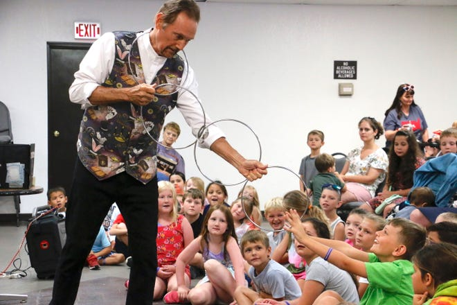 """""""Magic Jay"""" Zugai of Abilene entertains children with linking rings during the first of his two magic shows Thursday morning in the Adams Street Community Center."""
