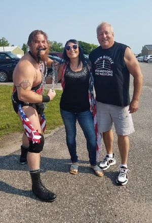 From left, UWE wrestler Mongo 'The Michigan Made Monster,' UWE ring girl Chanel and Turn Buckle Promotions CEO Jeff Charles pose for a photo before the Cheboygan 4th of July Parade on Saturday, July 3. Universal Wrestling Enterprises (UWE) will hold the 'Straits Summer Showdown' pro wrestling event at the Cheboygan Ice Pavilion on Saturday night. Doors will open at 6:30 p.m., followed by matches at 7:30 p.m.