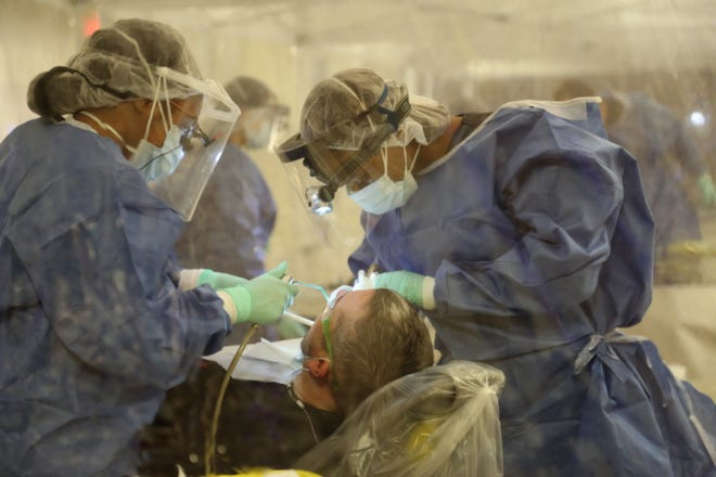 Volunteer dentists work on a patient's teeth during a recent free pop-up clinic hosted by the Tennessee-based nonprofit Remote Area Medical.