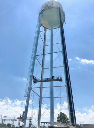 Workers from Utility Service Co. Inc., paint the North Gender Road water tower as part of scheduled maintenance, which took approximately three weeks to complete.