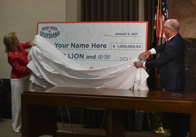 First lady Donna Edwards and Gov. John Bel Edwards unveil a giant check during a news conference June 17 at the Louisiana State Capitol in Baton Rouge.  They  announced that Louisiana will participate in a lottery, giving cash prizes and scholarships to residents who have been vaccinated against the coronavirus.