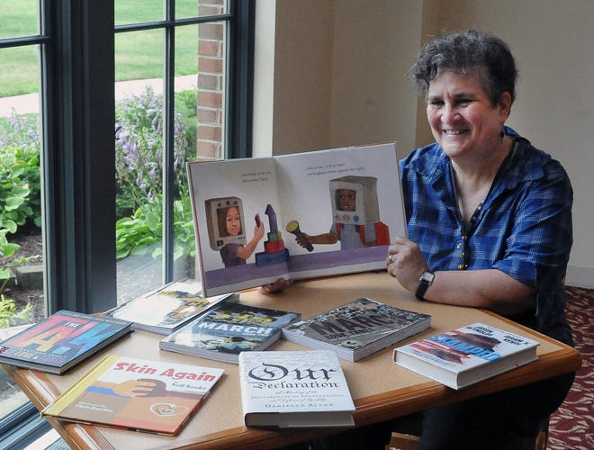 Susan Roberts, assistant director of the Wayne County Library, shows off some of the new books donated through a partnership with the Racial Justice Coalition and Buckeye Book Fair.