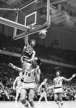 Lew Alcindor (33) of the Milwaukee Bucks seems to climb back of Philadelphia 76ers George Wilson (16) as Alcindor dunks second period field goal in their Eastern Division playoff game in Philadelphia, March 30, 1970. The Bucks set an NBA playoff scoring record routing the 76ers 156-120 to take 2-1 lead in best of seven semi-final series