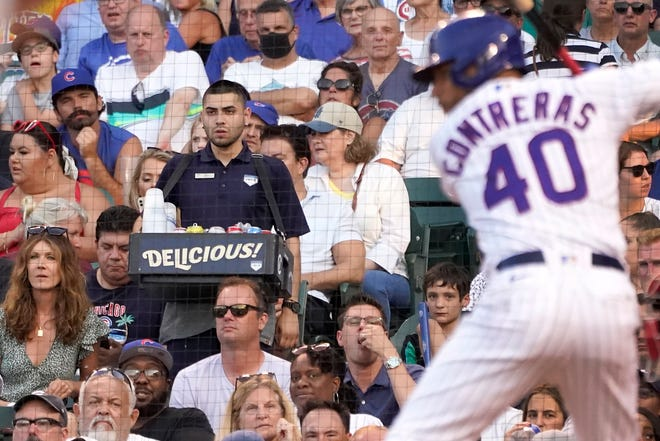 A concessions worker walks the aisle near home plate as Chicago Cubs' Willson Contreras waits for a pitch during the second inning of a baseball game against the Philadelphia Phillies on  Monday, July 5, 2021, in Chicago.