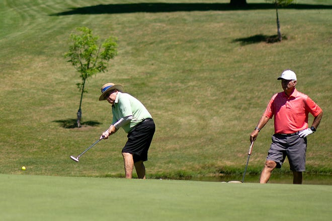 Jerry Toland putts on hole No. 3  while John Bicego waits his turn to hit the green in the first round of the 2020 Galesburg Men's All-City Golf Tournament on Friday, July 10, 2020 at Lake Bracken Country Club.