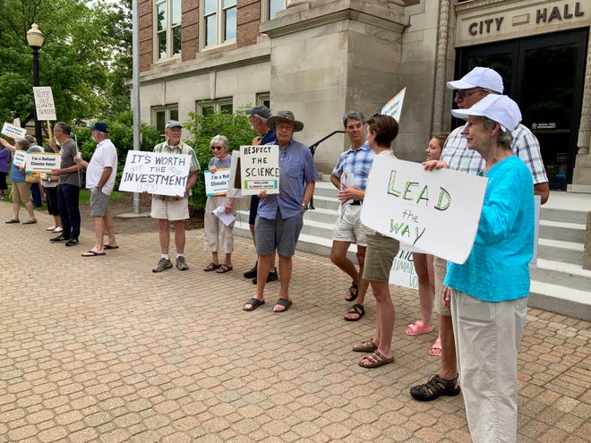 Climate activists outside Holland City Hall July 7, 2021, urged the council to adopt more aggressive goals to reduce carbon emissions in the city.