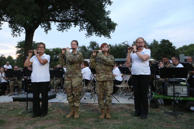 """From left, Sandy Skucius, Sgt. Samantha Soldani, Spec. Katrin Renyer and Valerie Powers play the piccolo portion of the """"Stars and Stripes Forever"""" song Tuesday night during the joint performance of the Hutchinson Municipal Band and the Kansas Army National Guard 35th Infantry Division Band."""