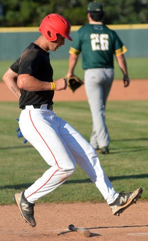 Newton Rebel Andrew Brautman avoids a bat while coming home to score against the Dodge City A's.