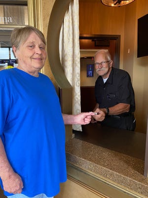 Movie goers will notice a familiar face behind the counter when going to the Lincoln Grand 8 Theater this weekend. Long time employee Richard Casad, right, sells a ticket to Charlene Maple, left, whose husband once worked for the theater. Five screens will be open this weekend to welcome movie lovers back to Lincoln's downtown theater.