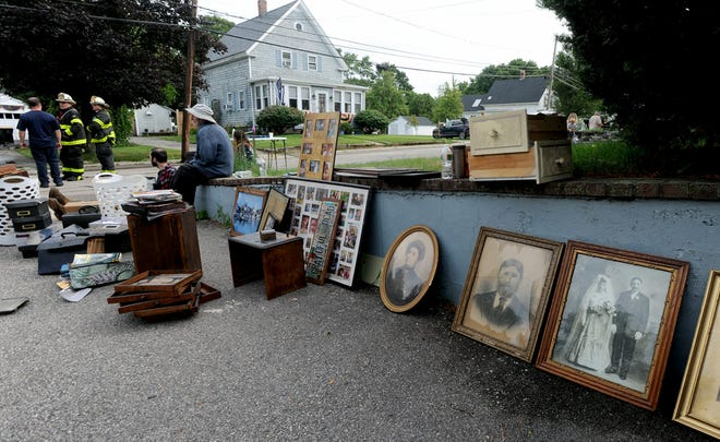 A resident of 71 North Park St. in Franklin sits with rescued photographs from his home after a two-alarm house fire started by a lightning strike at about 4 a.m. A cat died in the fire, July 8, 2021.