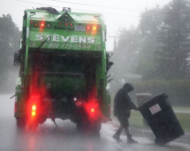 Employee from Stevens Disposal and Recycling of Petersburg empty the garbage along W. Dunbar Rd. in Raisinville Township. There is still a threat of more precipitation and next week could be wet as well, forecasters said.