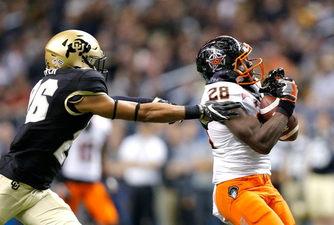 Oklahoma State's James Washington (28) makes a reception as Colorado's Isaiah Oliver (26) defends in the third quarter during the Valero Alamo Bowl in 2016.