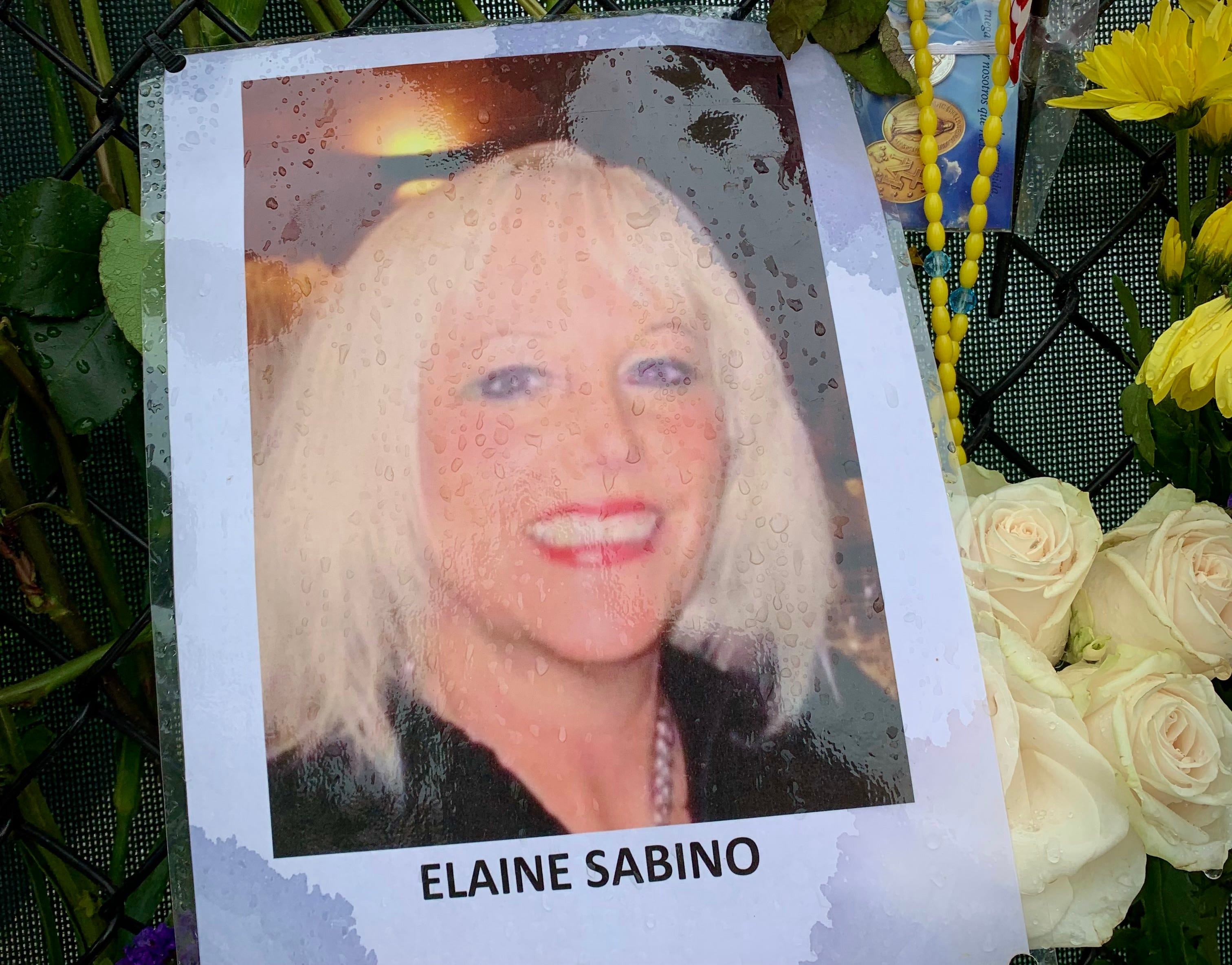 A photo of Elaine Sabino on the memorial wall near the site of the Champlain Towers South collapse. Sabino lived on the 12th floor with Richard Augustine. On July 7, after being listed as missing for two weeks, authorities notified her family that they had found her body.
