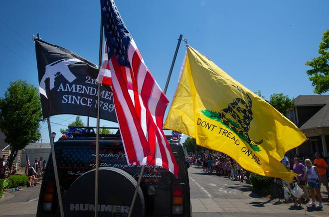 A Hummer with flags joins the Fourth of July parade in Creswell that went on without a permit.