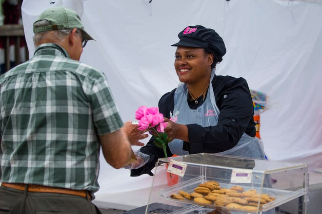 """Monnese Plummer sells cookies to Terry Bailey at her booth """"Fancy Delights"""" on Thursday at the St. Joseph County 4H fair in South Bend."""