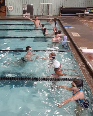 Kids take up lessons from the Sharks Aquatic Club at Shelby High School.